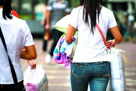 昨日,在华润万家门口,一位女孩购物后直接将购买的东西夹在腋下带回家。 时报记者 杜翠 摄