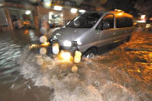 在广州白云区德康路,路面的积水已经淹到了大腿,一辆车正在经过。