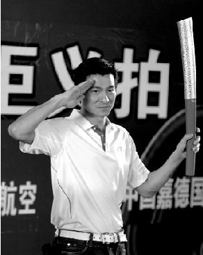 图为刘德华在义卖现场展示火炬。 新华社记者 赵颖全 摄