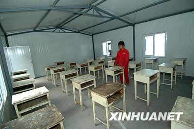 6月4日,工人在活动板房内安置书桌。 新华社记者丁海涛摄