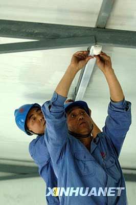 6月4日,工人在作为考场的活动板房内安装照明设备。 新华社记者丁海涛摄
