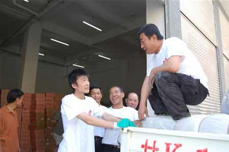 三个战友(后排)和一对父子(前排)正在搬运抗震救灾物资 记者阎世德/摄