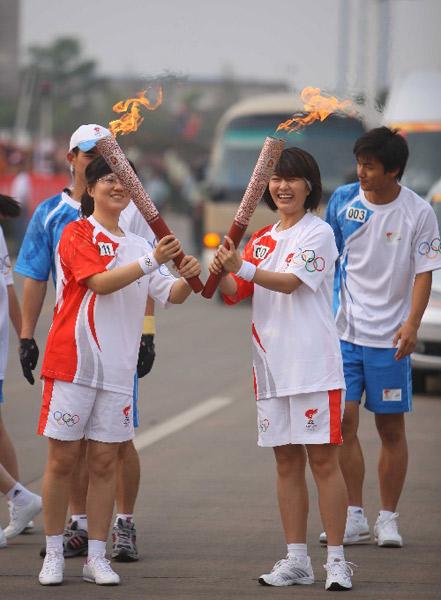 """火炬手刘娜(右二)与下一棒火炬手陈晓春交接后将两支火炬摆成英文字母""""V""""字形状。"""