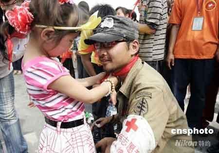 6月1日,在四川绵阳九州体育馆受灾民众安置区,儿童在节日为志愿者带上红领巾。 中新社发 杜洋 摄