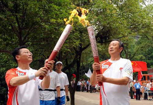 6月5日,火炬手毛岸平(右)与下一棒火炬手黄志刚交接。当日,北京奥运圣火在湖南韶山传递。 新华社记者刘力航摄