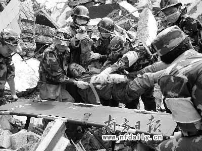 废墟上搜救到生还者,广州特警紧急用担架送往医院。龚宣摄
