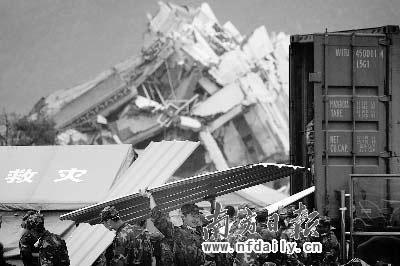 部队官兵在映秀镇漩口中学前的空地上卸载广东支援的活动板房。本报记者朱丹阳摄