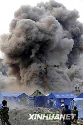 6月5日,几名记者在映秀镇地震危楼爆破现场拍摄。     新华社记者 李尕 摄