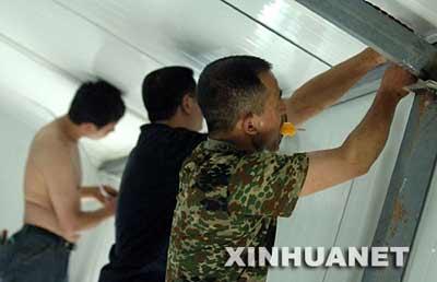 6月5日,在高考活动板房中,一位工人一边吃冰棍降温一边安装电路。新华社记者 丁海涛 摄