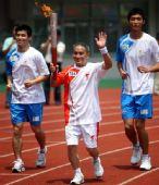 图文:奥运圣火在广西桂林传递 何可荣手持火炬