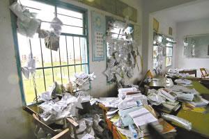 龙卷风把教师办公室内的课桌、书籍等吹得一片凌乱