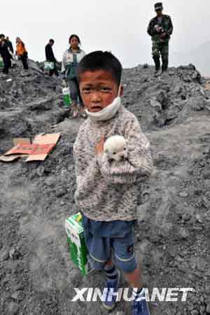 5月20日,在四川省什邡市仁和村,一位小朋友在领取食品的路上紧紧护住他的小狗。 新华社记者 何俊昌 摄
