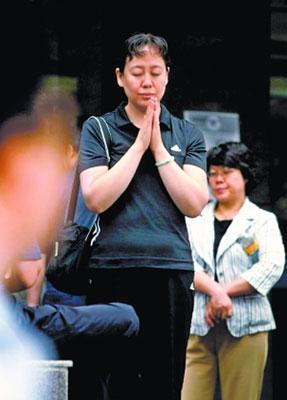 一位考生家长为自己的孩子默默祈祷。
