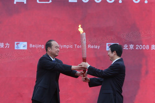 北京奥组委执行副主席王伟将火炬交给当地官员