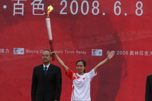 第一名火炬手周标亮展示火炬