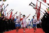 图文:奥运圣火在广西百色传递 王军跑向终点