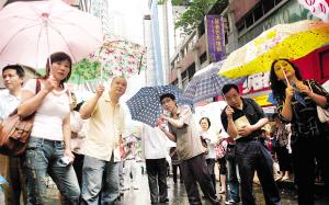 昨日,渝中考区29中考点,家长们在雨中等候参加考试的孩子 记者 李化 摄