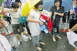 两个女儿正准备换上妈妈冒雨送来的拖鞋 记者 陈诚 摄