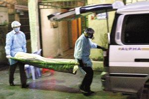 殡仪馆工作人员把腐尸抬上车运走。