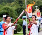 图文:奥运圣火在云南昆明传递 胡智绯交接