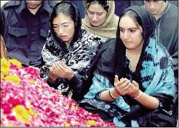 2007年12月29日,在巴基斯坦南部信德省胡达巴赫什堡村,贝·布托的两个女儿巴克塔瓦尔(右)和阿西法在母亲墓前祈祷。新华社/法新