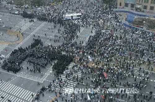 6月8日,韩国防暴警察在首尔街头阻挡准备前往总统府的抗议民众。虽然韩国总统李明博7日晚与美国总统布什就牛肉贸易问题通电话,但韩国民众反对恢复进口美国牛肉的示威游行仍未停止。新华社/路透