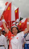 图文:奥运圣火在丽江传递 杨一奔手持火炬传递