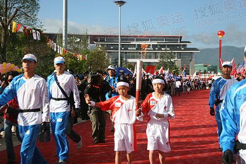 """来自四川汶川灾区13岁的张紫兰和1996年丽江地震时出生的丽江纳西族的和震生高举""""祥云""""传递"""