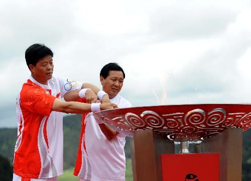6月11日,奥运火炬手彭耀文(左)与张国伟共同点燃圣火盆。当日,北京奥运圣火在云南香格里拉传递。