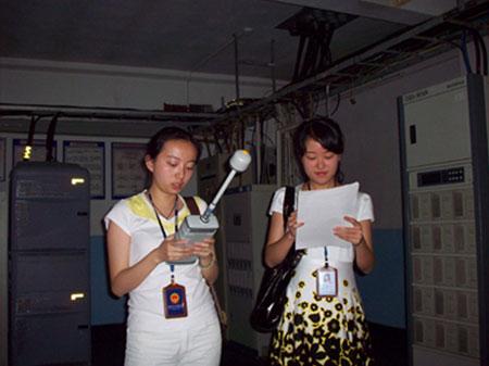 图:省辐射环境监理站工作人员在基站内部进行辐射监测