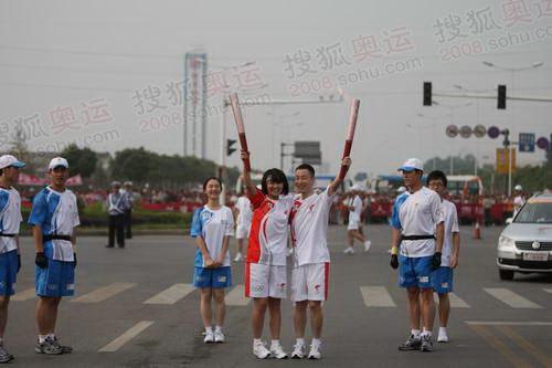 """第9棒火炬手高杰和第10棒刘娜等人在交接时,两人搭肩,高举祥云摆出代表胜利的""""V""""字造型"""