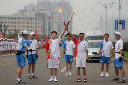 """汪涵在结束传递后,用自己手中的""""祥云""""火炬和下一棒火炬手摆出了一个象征胜利的""""V""""字造型"""