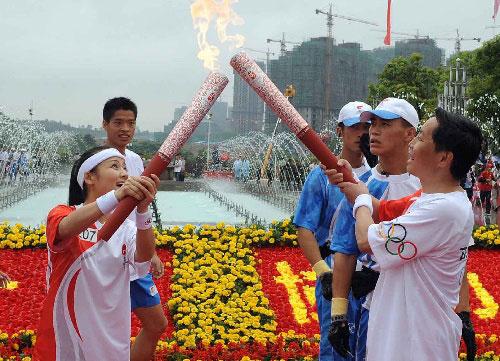 贵阳,2008年6月12日  (奥运火炬)(37)奥运火炬在贵阳传递  6月12日,奥运火炬手雷阿幼朵(前左)与袁周在传递过程中交接。当日,北京奥运火炬传递活动在贵州省贵阳市举行。  新华社记者丁林摄