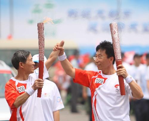 杭州火炬手王梓木(右)与残疾人火炬手打出爱心手势