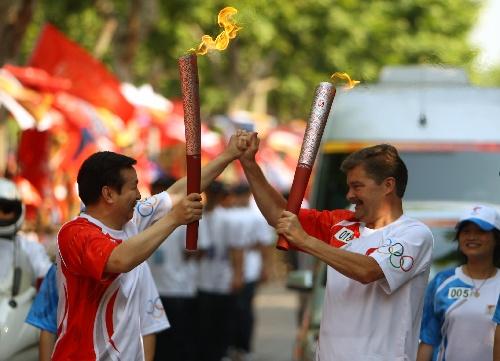 杭州火炬手坎德尔(右)与裴少军打出爱心手势