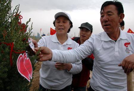 """宁夏奥运火炬手王有德(右)和孙仙梅(左)为自己种植的""""奥运树""""挂上爱心寄语牌,深深祝福2008北京奥运取得成功"""