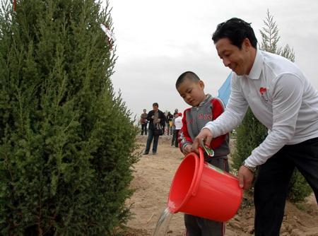 宁夏奥运火炬手与小朋友一起植树