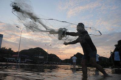6月13日,一位老人在一片泽国的广西柳州市柳石路上撒网捕鱼。 新华社发