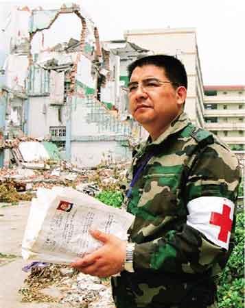 ▲陈光标捡起废墟中的学生登记表。江苏黄埔供图