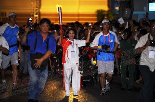 胡志明市副市长为第一棒火炬手正要从媒体车的侧面经过