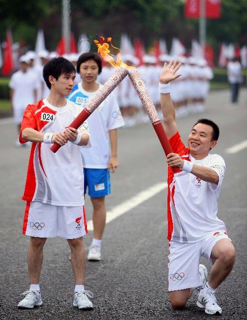 6月16日,火炬手程杨(右)与下一棒火炬手廖小波交接。当日,北京奥运圣火在重庆传递。 新华社记者邢广利摄