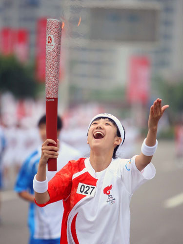 6月16日,火炬手胡悦手持火炬传递。当日,北京奥运圣火在重庆传递。 新华社记者邢广利摄