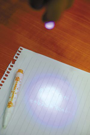 资料图片:隐形笔的墨水中含有荧光分子,只有在紫外灯照射下,分子才能感光。上图中的数学公式如果没有灯光的照射是显现不出来的。