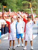 图文:奥运圣火在新疆石河子传递 黄勇交接握手