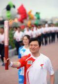 图文:奥运圣火在新疆石河子传递 汤捷手持火炬