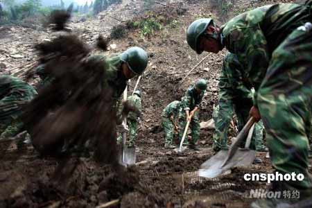 6月8日,中国空降兵某部进村入户之后,在四川省什邡市蓥华镇清理通往麻柳坪盘山公路上的滑坡,帮助当地石门村恢复交通。图为官兵在麻柳坪盘山公路上清理滑坡碎石。中新社发谭超 摄
