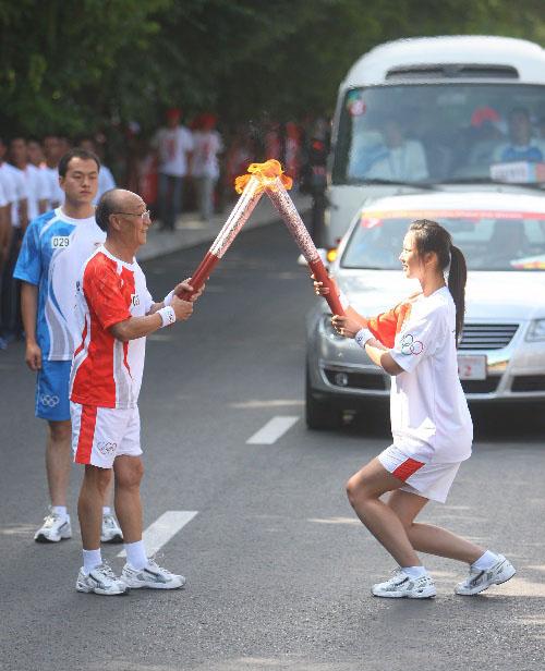 火炬手申秉昌(左)与下一棒火炬手卞紫毓交接