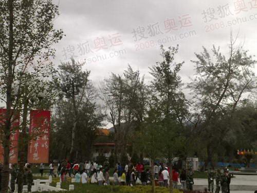 拉萨市民在起跑现场雨中迎火炬