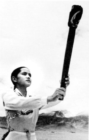 藏族姑娘达娃央宗在念青唐古拉峰,高举由她亲手点燃的亚运圣火种