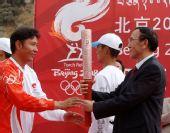 图文:奥运圣火在拉萨传递 尼玛次仁递交火炬